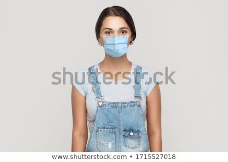 portrait of standing woman wearing denim overalls Stock photo © phbcz