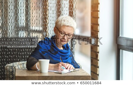 Mature  business woman with pen in her hand Stock photo © annakazimir