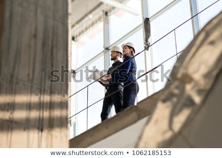 Stock photo: Man on construction site holding pole