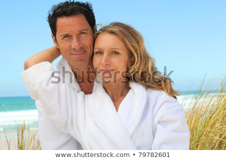 Man and woman in toweling robes on the beach Stock photo © photography33