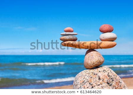 balanced stones pebbles stacks against blue sea stock photo © ewastudio