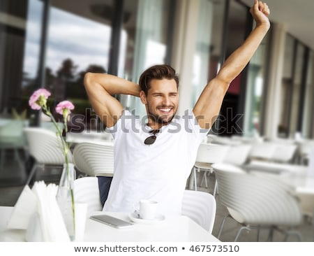 Handsome man relaxing with arms stretched  Stock photo © wavebreak_media