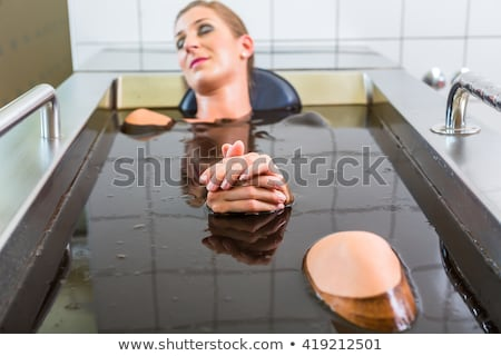 Senior woman enjoying mud bath alternative therapy Stock photo © Kzenon