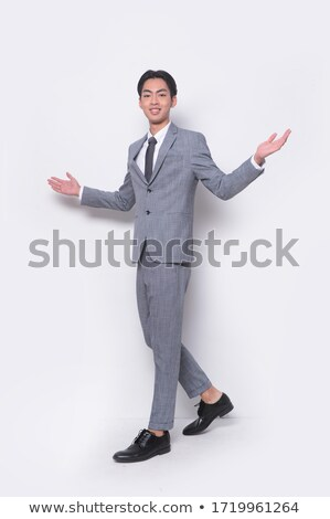 Attractive confident young businessman standing with hands on hips Stock photo © deandrobot