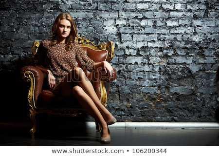 Portrait of fashionable model sitting in armchair. Stock photo © julenochek
