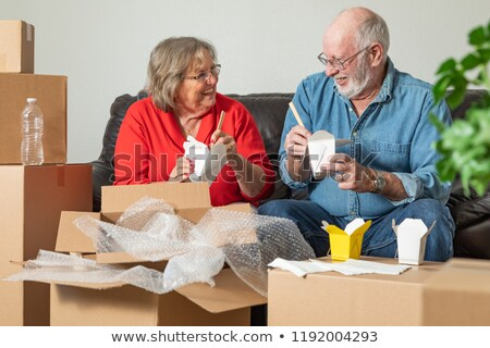 Stockfoto: Senior Couple Enjoying Chinese Food Surrounded By Moving Boxes