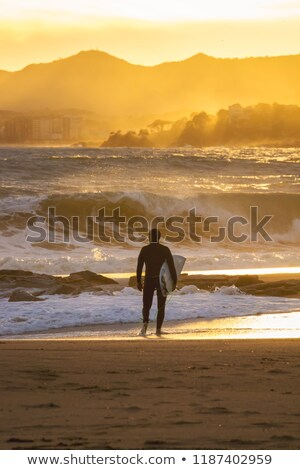 Windy day on the spanish coastal in Palamos with a surfer on the beach Stock photo © digoarpi