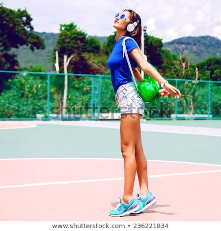 happy young sports woman posing outdoors listening music stock photo © deandrobot