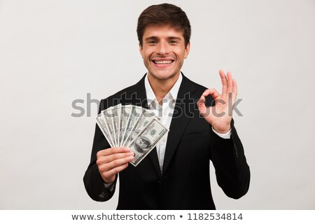 Happy businessman standing isolated holding money make okay gesture. Stock photo © deandrobot