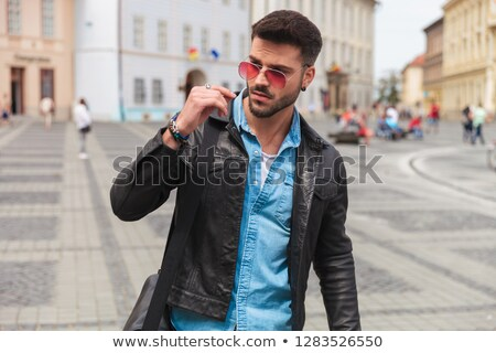 young man having a city break looks down to side Stock photo © feedough