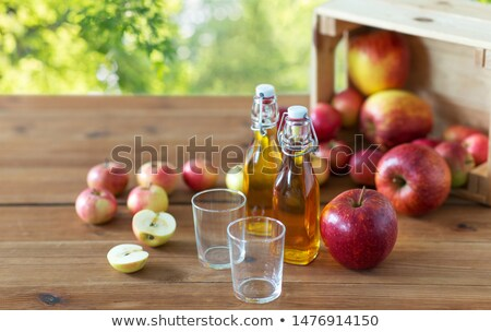 Glasses of homemade organic apple cider with apples in box Stock photo © artsvitlyna