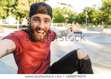 Young skater guy sit in the park with skateboard take selfie by mobile phone. Stock photo © deandrobot
