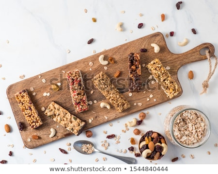 Organic cereal granola bar with berries on marble board with honey spoon and jar of oats and coconut Stock photo © DenisMArt