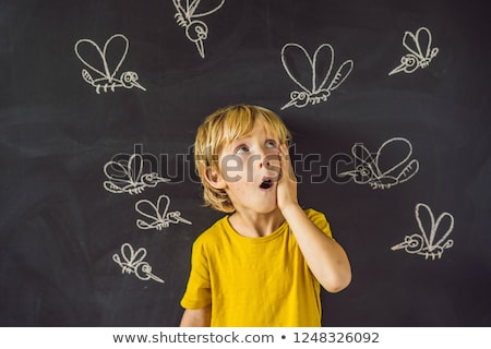 The boy is bitten by mosquitoes on a dark background. On the blackboard with chalk painted mosquitoe Stock photo © galitskaya