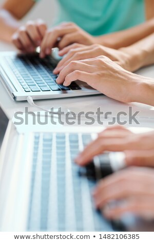 One of young contemporary co-workers or classmates typing on laptop keypad Stock photo © pressmaster