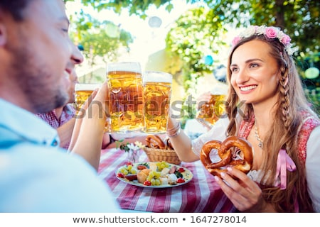 Couple clinking glasses with huge amounts of beer in Bavarian pub Stock photo © Kzenon