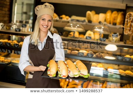 Female baker posing with various types of sandwiches in the bake Stock photo © boggy