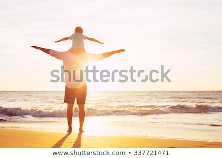 happy father and son having quality family time on the beach on sunset on summer holidays lifestyle stock photo © galitskaya