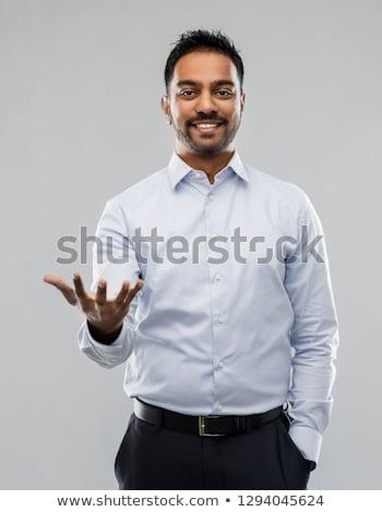 indian businessman holding something invisible Stock photo © dolgachov