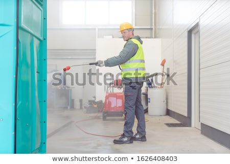 Worker cleaning a rental or mobile toilet Stock photo © Kzenon