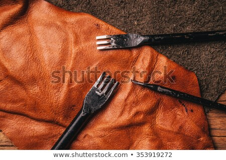 Punching holes in leather piece Stock photo © pressmaster