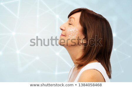 senior woman with low poly grid on her cheek Stock photo © dolgachov