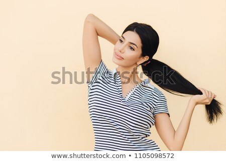 Pensive dark haired female makes pony tail, has full lips and pleasant appearance, wears casual outf Stock photo © vkstudio