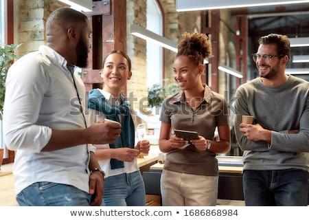 Horizontal shot of happy male office worker has coffee break at cafeteria, drinks hot beverage, dres Stock photo © vkstudio