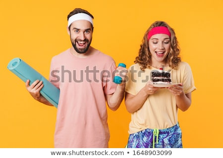 Portrait of man holding mat and dumbbell while woman holding cak Stock photo © deandrobot