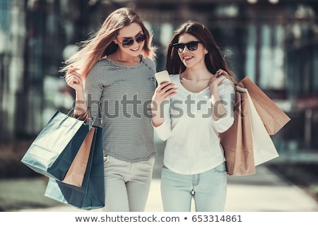 Two friends with shopping bags holding mobile phones Stock photo © photography33