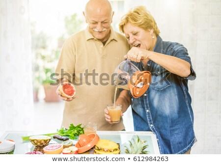 Elderly lady squeezing orange juice Stock photo © photography33