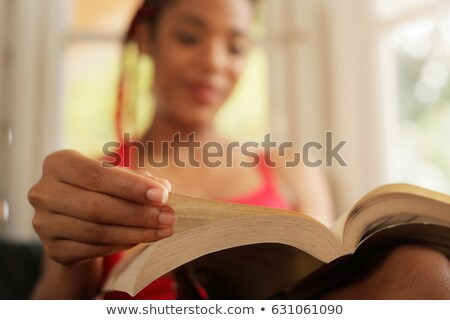 concentrated woman reading a book sitting on a sofa stock photo © wavebreak_media