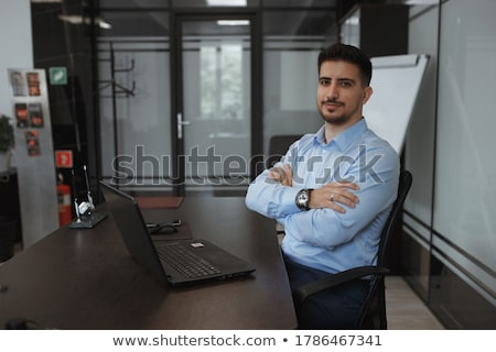 Happy executive sitting in front of laptop with arms on table Stock photo © HASLOO