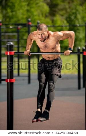 Topless Muscular Man Bending an Exercise Bar Stock photo © stryjek