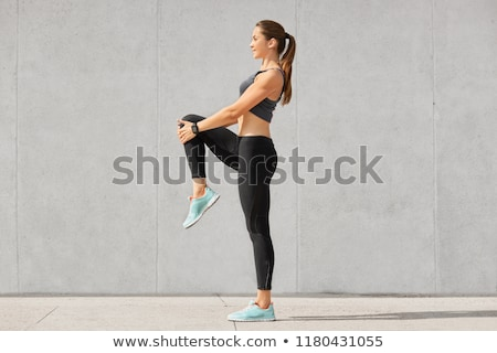 Fitness woman warming up at stadium Stock photo © deandrobot