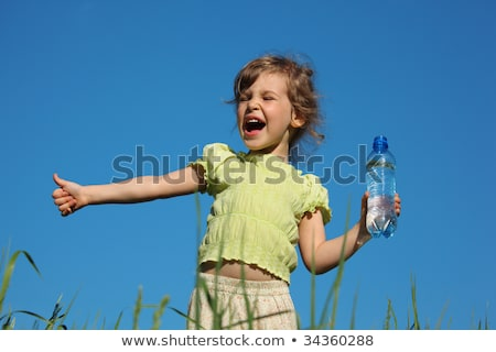 Stock photo: screaming girl in grass with plastic bottle with water