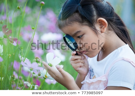 happy little girl looking through magnifying glass stock photo © dolgachov