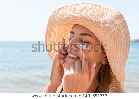 Stock photo: happy young woman in swimsuit applying sunscreen