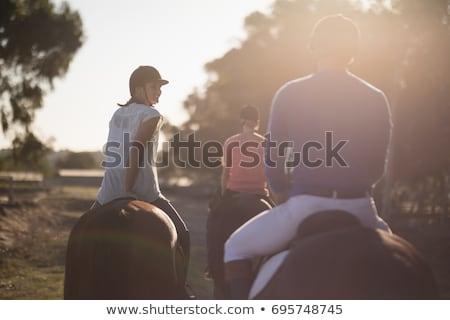 trainer training women in riding horses at barn stock photo © wavebreak_media