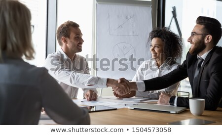A Middle Eastern and a caucasian businessman shaking hands stock photo © monkey_business