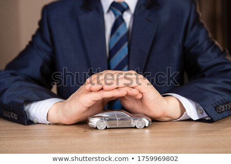 Car insurance. Small silver car covered by hands.  Stock photo © sqback