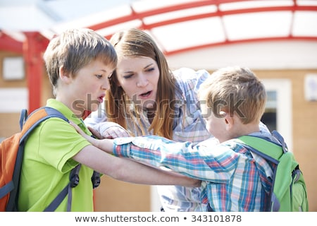teacher stopping two boys fighting in playground stock photo © lopolo