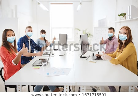 group of businesswomen showing thumbs up at office stock photo © dolgachov