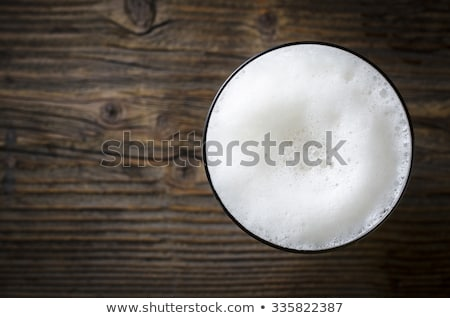 Glass of lager beer with foam and bubbles on vintage wooden board on black background.  Stock photo © DenisMArt