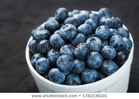 fresh raw organic blueberries on round vintage wooden board on stone kitchen background space for t stock photo © denismart