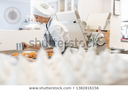 Patissier in her bakery shop with lots of meringue Stock photo © Kzenon