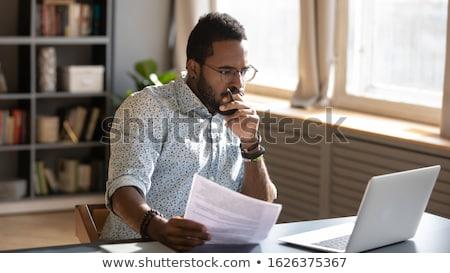 Jovem africano corretor olhando financeiro dados Foto stock © pressmaster