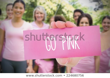 Hands holding card with pink breast cancer awareness women Stock photo © wavebreak_media