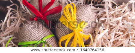 Banner of Easter eggs in twine on brown wooden background. Stock photo © Illia