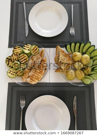 Baked potatoes with vegetables and croutons on a tare. Grilled zucchini with grilled chicken fillet Stock photo © ElenaBatkova